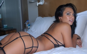 Black-haired gal in sexy lingerie loves to pose undressed in bedroom