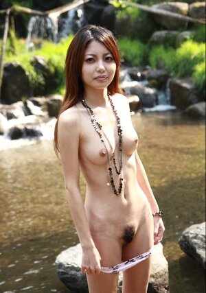 Sweet asiatic lassie walks alone and slowly undresses on camera