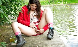 Minx in red jacket comes to a deserted pond for having fun with shaggy vag